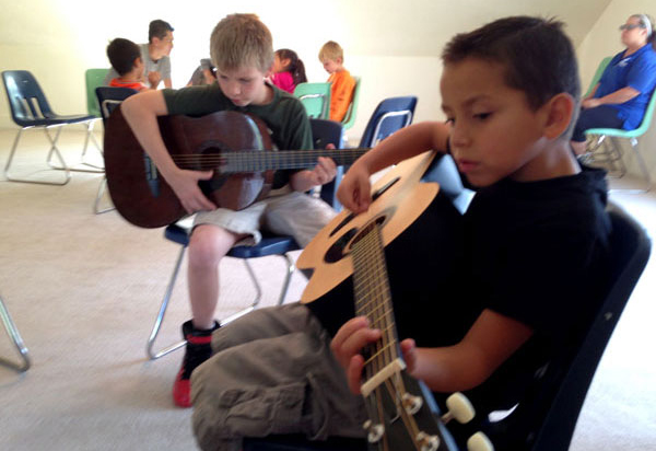 Two kids playing a Guitar